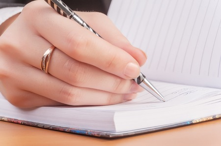 businesswoman writes mission for business plan in office photo