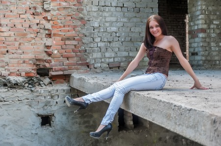 Beautiful brunette girl against the background of the ruins photo