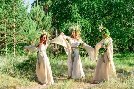 Attractive Women with Wreath of Flowers walking in forest  Ivan Kupala Holiday Celebration  photo