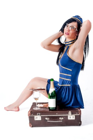 Attractive young stewardess with cash and wine bottle on old-fashioned suitcase photo