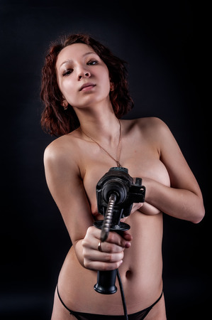 Portrait of a beautiful topless woman holding drill photo