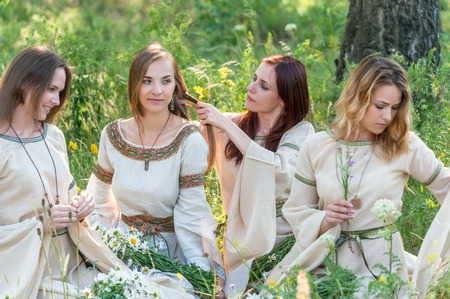 Attractive women in traditional russian clothes relaxing at nature background  Ivan Kupala Holiday Celebration  photo