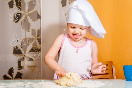 Cute little cook girl molds cookies from dough photo