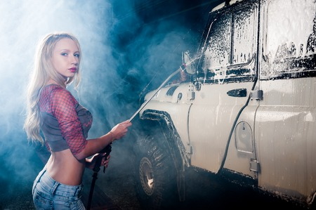 provocative women: Pretty young woman washing offroad car by foam hose Stock Photo