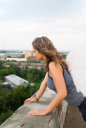 Attractive woman with angel wings on building roof looking over city photo