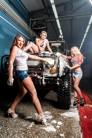 Pretty young women washing offroad car by sponge photo
