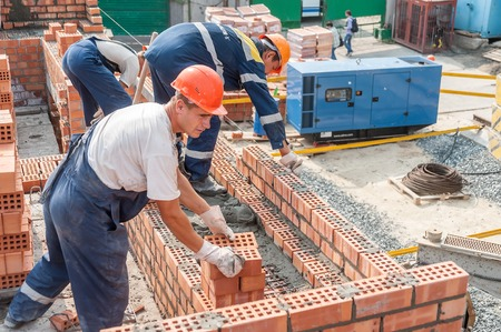 Tyumen, Russia - July 31, 2013  JSC Mostostroy-11  Construction of a 18-storeyed brick residental house at the intersection of streets of Nemtsov and Tsiolkovsky  Team of bricklayers behind work