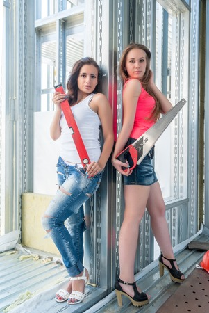 Two sexy women with meausering level and handsow on construction site photo