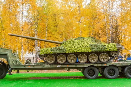 Nizhniy Tagil, Russia - September 27  2013  Russia Arms Expo-2013 exhibition  Tank under camouflage network on truck platform