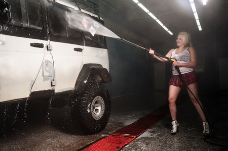 Young woman washing offroad car by water hose photo