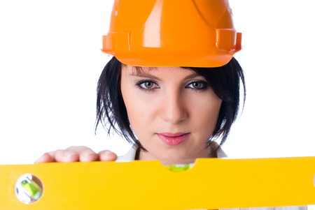 Young pretty worker with protection helmet and level at isolated background photo