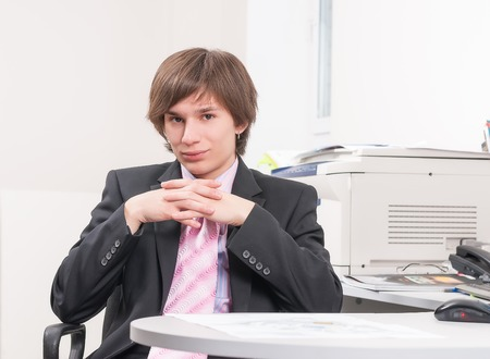 Young pretty businessman sitting on office workplace photo
