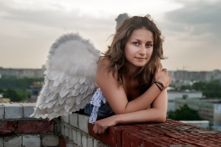 Young beautiful woman with angel wings on building roof looking over city photo