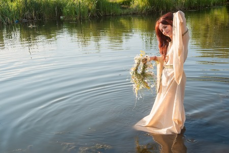 Attractive red-hair woman with national dress in water of lake  Russian traditional Ivan Kupala holiday celebration photo