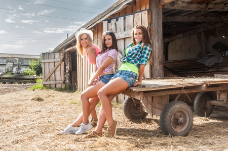 Three attractive women sitting on cart in front of stable entrance photo