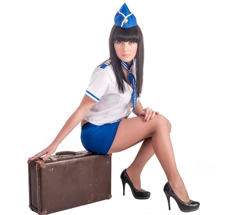 Attractive young stewardess sitting on old-fashioned suitcase photo