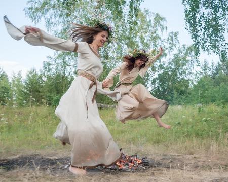 Two beautiful women with wreath of flowers jump through bonfire  Ivan Kupala Holiday Celebration  Russia photo