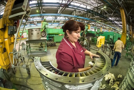 Tyumen, Russia - November 14, 2007  JSC Tyumenskie Motorostroiteli  Plant on production and repair of aviation engines   Woman cleans part for aviation engine