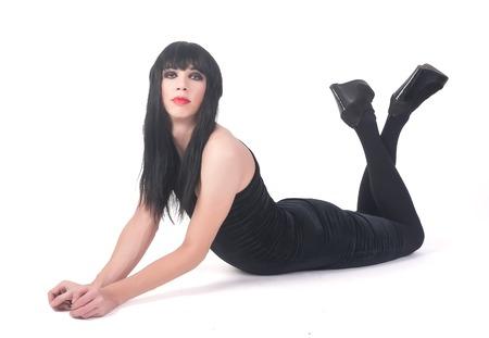 transexual: Hombre lindo travesti vestido de mujer yace sobre el fondo blanco