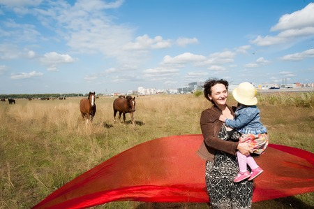 Smiling mother with little daughter over horses background at summer day photo