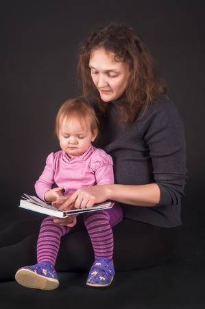 Attractive mother showing images in a book to her cute little daughter over black background photo
