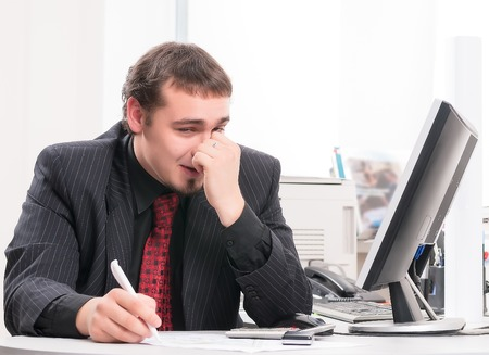 Young businessman works in office and scratches nose photo