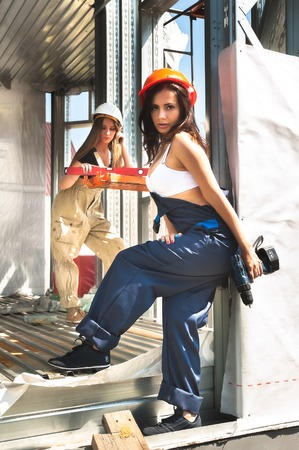 Beautiful sexy woman construction worker in hard hat with battery drill and level photo