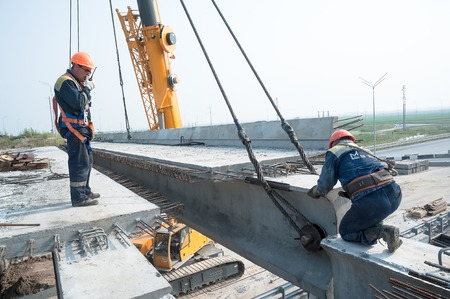 Tyumen, Russia - July 31, 2013: JSC Mostostroy-11. Bridge construction for outcome of Tobolsk path and Bypass road round Tyumen. Engineer with handheld transceiver controls equalization of bridge span