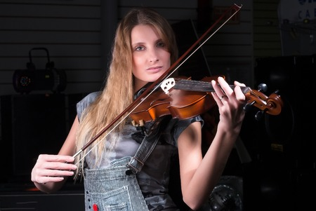 Young beautiful woman plays music on violin photo