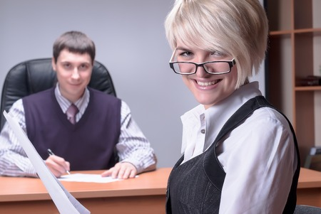 Smiling business woman studies document over colleague background in office photo