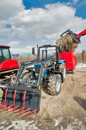 specialized job: Tyumen, Russia - April 04. 2014: IV Tyumen specialized exhibition. Agricultural wheel loader demonstration Editorial