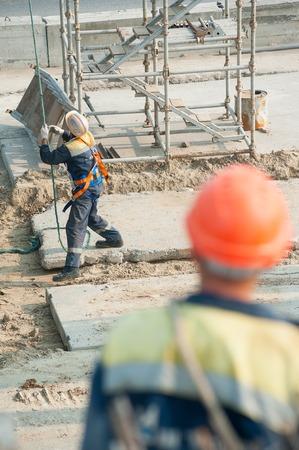 abastecimiento: Tyumen, Rusia - 31 de julio 2013: JSC Mostostroy-11. Construcci�n de puente para el resultado de la trayectoria de Tobolsk y carretera de circunvalaci�n alrededor de Tyumen. Niveles trabajadores provisi�n de placa de elevaci�n por gr�a Editorial