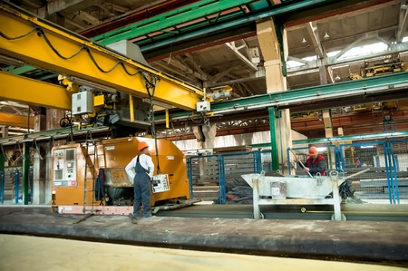 Tyumen, Russia - August 13, 2013: Block making department at construction material factory ZHBI-5. Workers operate machine on filling of concrete plates