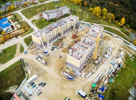 residental: Tyumen, Russia - September 26, 2014: Aerial view on lifting cranes on construction site of residential house in Vinzili. Tyumen, Russia