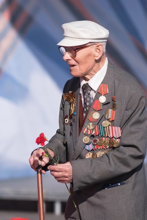 Tyumen, Russia - May 9. 2009: Victory Day in Tyumen. Old veteran of World War II at tribunes waiting for parade