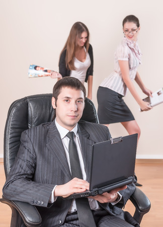 Business man works with laptop over female colleagues background photo