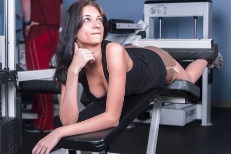 Young pretty sport woman trains in fitness center photo