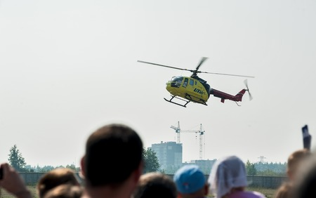 heliport: Tyumen, Russia - August 11, 2012: On a visit at UTair airshow in heliport Plehanovo. People waiting of landing Eurocopter AS-350