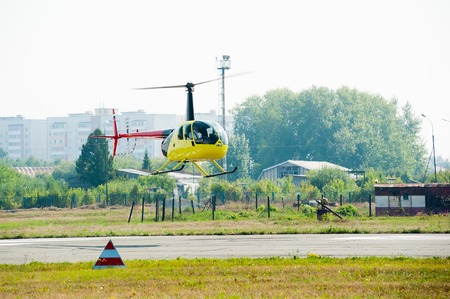 heliport: Tyumen, Russia - August 11, 2012: On a visit at UTair airshow in heliport Plehanovo. Pilot of Eurocopter AS-350 shows flying opportunities Editorial