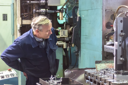 Tyumen, Russia - November 14, 2007: JSC Tyumenskie Motorostroiteli (Plant on production and repair of aviation engines). Elderly worker watches processing of detail on milling machine