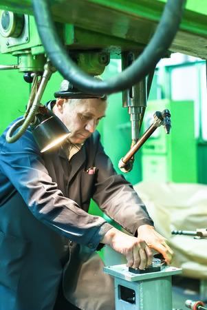 fettler: Tyumen, Russia - November 14, 2007: JSC Tyumenskie Motorostroiteli. Plant on production and repair of aviation engines. Elderly worker watches processing of detail on milling machine Editorial