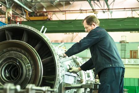 aviation: Tyumen, Russia - November 14, 2007: JSC Tyumenskie Motorostroiteli. Plant on production and repair of aviation engines. Elderly mechanic assembles aviation engine