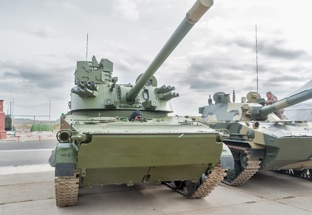 Nizhniy Tagil, Russia - September 25 2013: Visitors examine military equipment on exhibition range. Airborne tracked armoured personnel carrier BMD-4M with additional protection