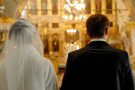 Groom and bride face in church an altar on wedding ceremony photo