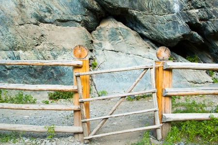 ancient pass: Kucherla, Russia - July 23, 2005: Ancient petroglyphs or rock engravings in Mountain Altai. Historical place is fenced with wooden fence Stock Photo