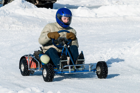 carting: Tyumen, Russia - February 22, 2015: Ice autodrome Ice cult on Alebashevo lake. Man is driving Go-kart with speed on karting track Editorial
