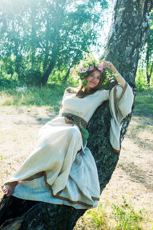 lays down: Attractive Woman with Wreath of Flowers lays down on birch (Ivan Kupala Holiday Celebration) Stock Photo