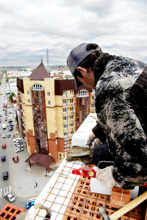residental: Tyumen, Russia - May 23, 2008: Construction of 18 floor brick residental house at intersection of streets of Gercena and Chelyuskincev. Bricklayer behind work. It is demolished because of bad base Editorial