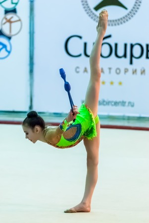 sports complex: Tyumen, Russia - April 4, 2015: All-Russian competitions in rhythmic gymnastics Spring grace. Sports complex Priboy. Young beautiful girl shows own skill in exercise with maces Editorial
