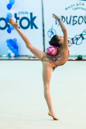 sports complex: Tyumen, Russia - April 4, 2015: All-Russian competitions in rhythmic gymnastics Spring grace. Sports complex Priboy. Young pretty girl shows own skill in exercise with ball